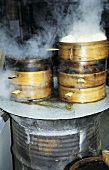 Steaming Chinese steamed noodles in basket at market