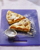 Quark tart with apricots, sieve with icing sugar in front