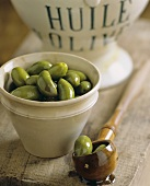 A bowl of green olives in olive oil