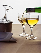 Pouring white wine beside cooler and filled glass
