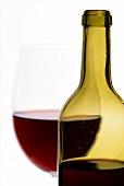 Rotweinflasche mit Glas im Hintergrund (Ausschnitt)