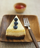 A piece of cheesecake, with blueberry garnish