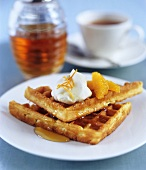 Orange waffles with cream and maple syrup and a cup of tea