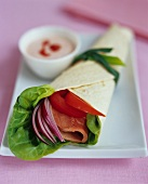Wrap with lettuce and ham filling and a bowl of dip