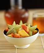 Fruit salad with carambola stars in bowl