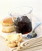 Blueberry and cinnamon jelly in jar, scones beside it