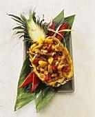 Schweinefleisch süss-sauer, serviert in ausgehöhlter Ananas