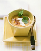 Pumpkin soup with sour cream, coriander, chili powder