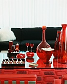 A red and black seating area - Spoon canapés, glass vases and candles on a glass table in front of a sofa