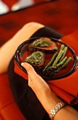 Woman holding plate of roast beef with pesto & asparagus