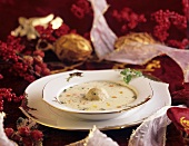 Creamed goose soup with soup dumplings on Christmassy plate