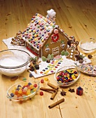 Gingerbread house with bowl of decorating ingredients