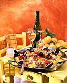 Paella in a classic paella pan on yellow table
