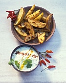 Baked potato wedges with spicy yoghurt dip