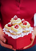 Profiteroles with raspberry cream on gift box