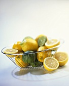 Lemons and limes, cut open and whole in wire basket