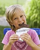 Mädchen beisst in Tafel Schokolade