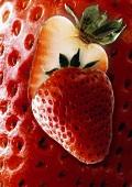 Halved strawberry, background: enlarged strawberry