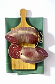 A black pudding with a piece cut on a wooden board