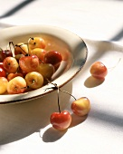 Yellowy-red cherries on and beside a plate