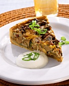 A piece of mushroom quiche on a plate
