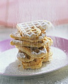 Heart-shaped butter waffles being dusted with icing sugar