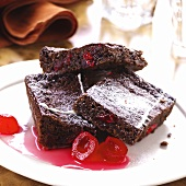 Three pieces of chocolate cake with glace cherries