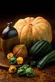 Still life with pumpkins, courgettes and pumpkin seed oil