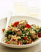 Pan-cooked wheat and vegetable dish with pieces of sausage
