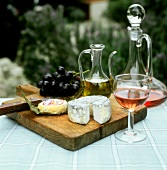 Still life with goat's cheese, rose wine and grapes