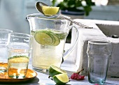 Light wine and tonic punch with lime in jug and glasses