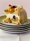 A piece of cream gateau with fruit and marzipan topping