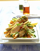 Raw carrot and cucumber salad with sliced chicken breast