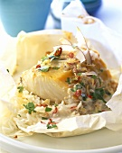 Cod with spicy coconut sauce baked in baking paper