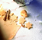 Cutting cinnamon stars out of sweet pastry (baking still life)