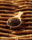 Black tea mixture on wooden tea measuring spoon