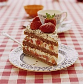 A piece of chocolate sponge cake with fresh strawberries