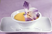 Vanilla blancmange in bowl, decorated with a flower