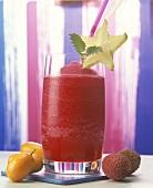 Frozen strawberry drink in glass, fresh fruit beside it