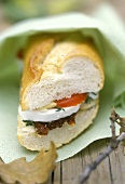 Baguette sandwich with goat cheese & tomato to eat on the move