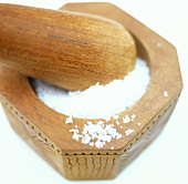 Coarse sea salt in wooden mortar