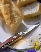 Baguette in the piece and sliced with jack-knife on plate