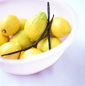 Lemons with vanilla pods in a white dish