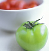 Whole green tomato in front of a bowl of red tomatoes