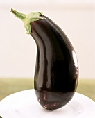 Whole aubergine standing on plate