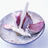 Cloves of garlic with remains of the bulb on ceramic plate