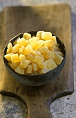 Terracotta bowl of candied pineapple on a wooden board