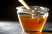 Honey spoon in jar of chestnut honey