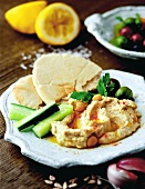 Kichererbsendip (Hummus) mit Fladenbrot und Gurken