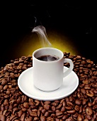 Cup of steaming coffee on coffee beans